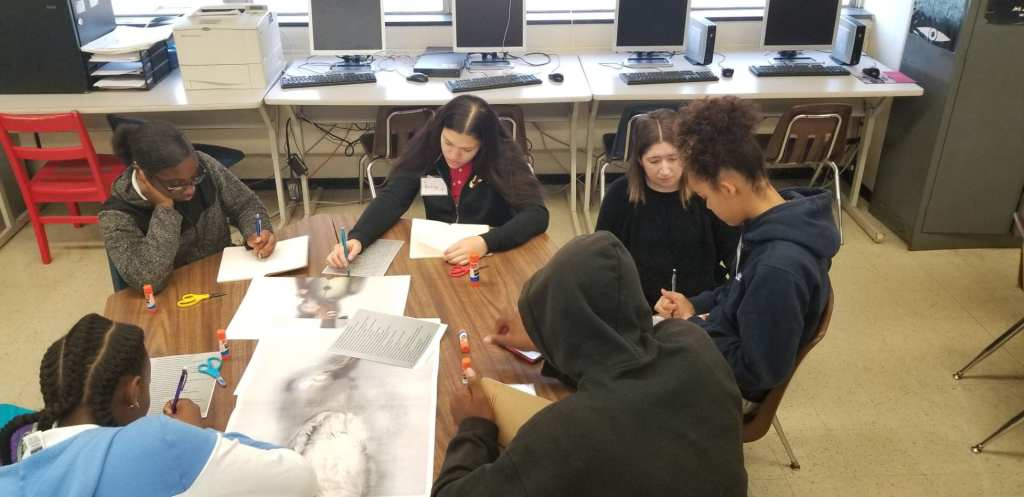 Students sitting around a table writing and working with Ann Hamilton's art
