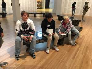 Students in an art gallery looking, thinking, writing.